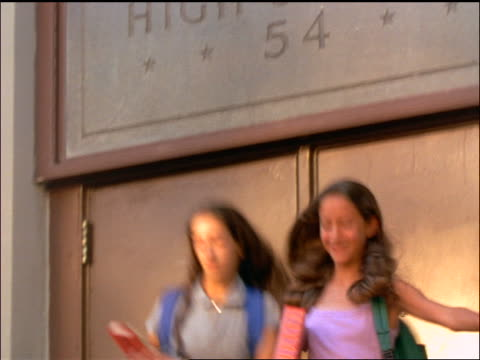 slow motion tilt down sign above junior high school to 2 schoolgirls rushing down steps of entrance - 1998 stock videos & royalty-free footage