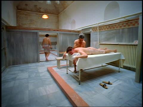 vidéos et rushes de slow motion tilt down tilt up ceiling to man in towel walking + second man getting massage in turkish bath / istanbul - se faire dorloter