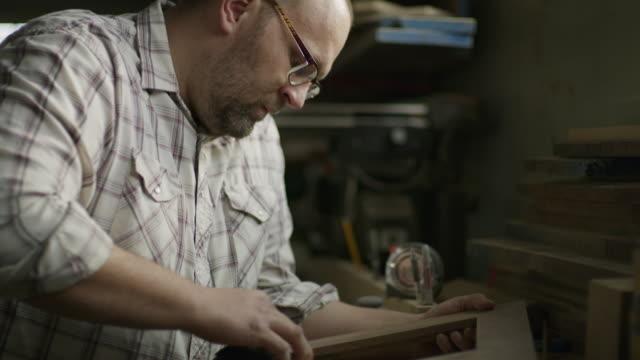 slow motion tilt down to man sanding wood frame in workshop / provo, utah, united states - provo video stock e b–roll