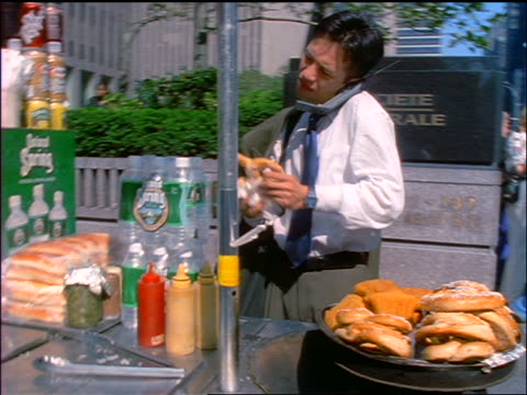 slow motion tilt up Asian businessman talking on cellular phone buys pretzel from vendor on NYC sidewalk