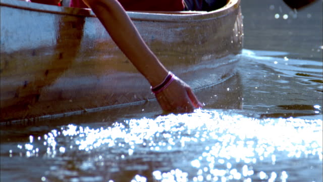 vidéos et rushes de slow motion tilt up couple rowing canoe on lake / woman's hand scooping water - bateau à rames