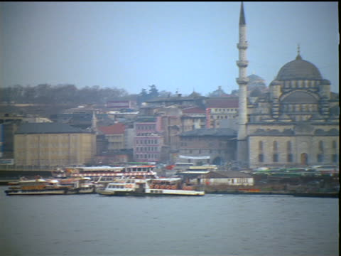 slow motion tilt up pan from boats on water to yeni (new) mosque near coast / hagia sofia in background / istanbul - yeni cami mosque stock videos and b-roll footage