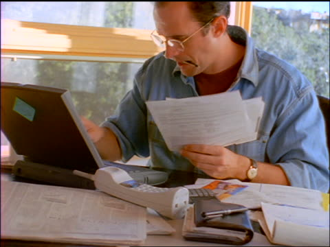 slow motion tilt up man with eyeglasses + pen in mouth looking at bills while using laptop computer - 1998 stock-videos und b-roll-filmmaterial