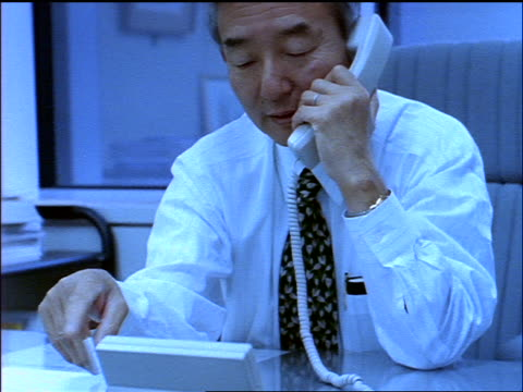 BLUE slow motion tilt up middle-aged Japanese businessman talking on phone at desk