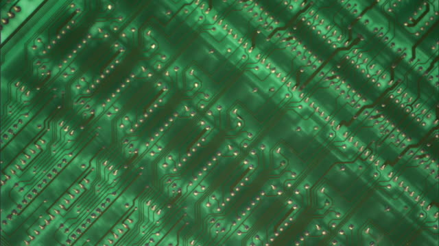 Slow motion tilt up of a green circuit board at a dutch angle; as tilt up occurs, the focus blurs.