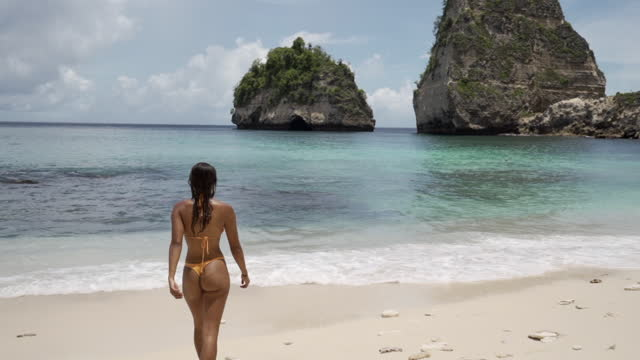 vídeos de stock, filmes e b-roll de slow motion tilt up of a woman walking into the shallow surf and waves of a tropical turquoise beach with rocks and sunny sand - nusa penida & lombok, bali - swimwear
