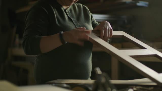 slow motion tilt up on woman sanding wood frame in workshop / provo, utah, united states - provo video stock e b–roll