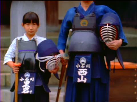 slow motion tilt up PORTRAIT Japanese man + girl standing holding kendo gear outdoors / Japan
