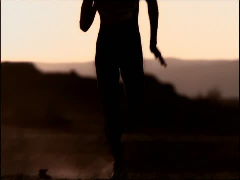vídeos de stock, filmes e b-roll de slow motion tilt up silhouette of black male athlete running toward camera in desert / namibia, africa - áfrica meridional