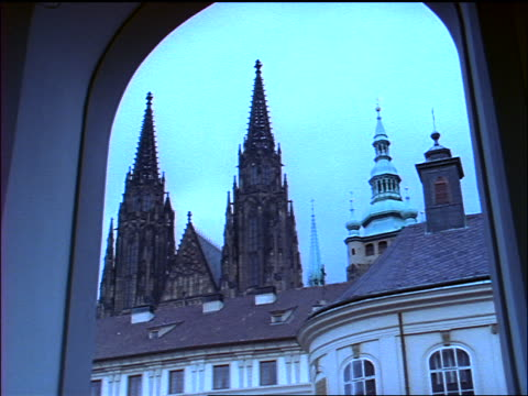 BLUE slow motion tilt up spires of Prague Castle seen thru archway / Czech Republic