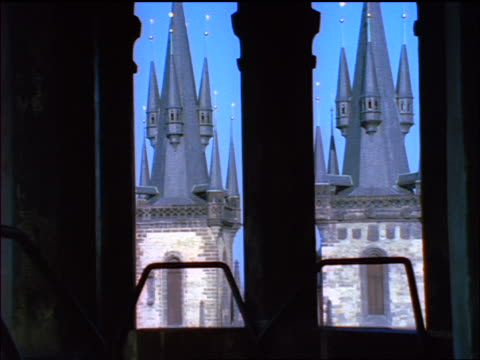 blue slow motion tilt up thru silhouette of arched windows of spires of tyn church / prague, czech republic - altstädter ring stock-videos und b-roll-filmmaterial