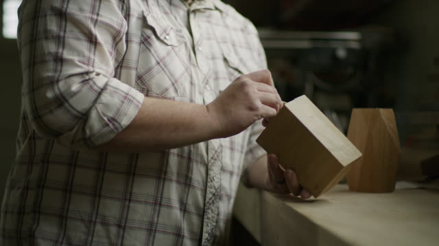 slow motion tilt up to man marking block of wood with pencil in workshop / provo, utah, united states - provo video stock e b–roll