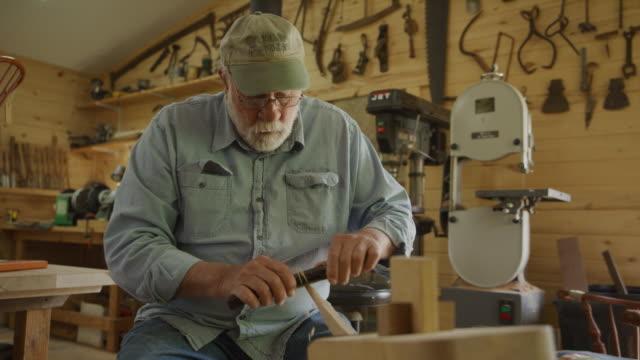 vídeos y material grabado en eventos de stock de slow motion tilt up to man shaving wood in workshop / spring city, utah, united states - encuadre de tres cuartos