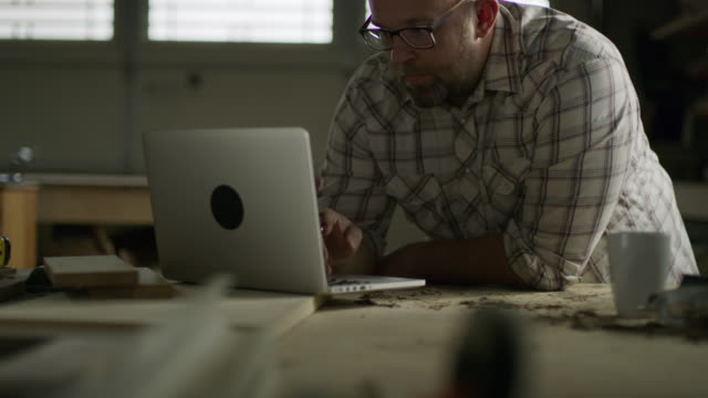 slow motion tilt up to man using laptop in workshop / provo, utah, united states - provo video stock e b–roll