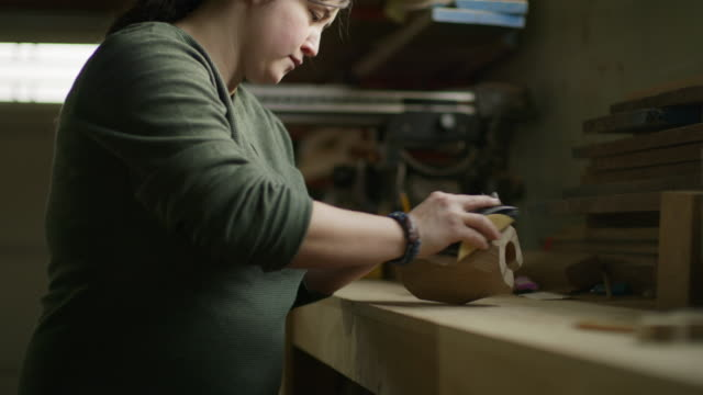 slow motion tilt up to woman sanding wood block in workshop / provo, utah, united states - provo stock videos & royalty-free footage