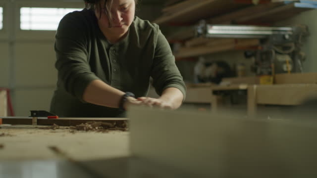 slow motion tilt up to woman sanding wood plank in workshop / provo, utah, united states - provo stock videos & royalty-free footage