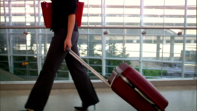 Slow motion tilt up woman pulling suitcase through airport
