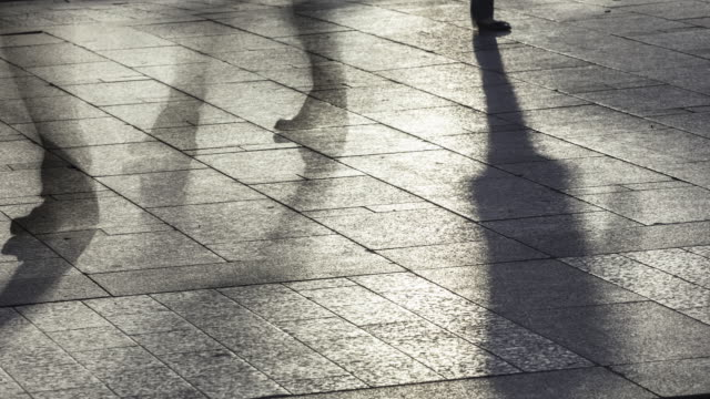Slow motion time lapse of pedestrian mouvements and shadows in backlight on pavement