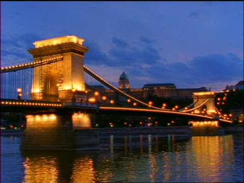 slow motion time lapse traffic + clouds over chain bridge on danube river / sunset to night / budapest, hungary - chain bridge suspension bridge stock-videos und b-roll-filmmaterial