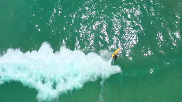 slow motion top view of man surfer surfing on waves - tahiti stock videos & royalty-free footage