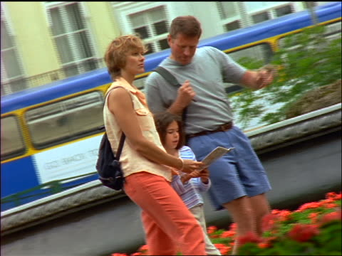 stockvideo's en b-roll-footage met slow motion pan tourist couple + daughter looking at guidebook while walking on city street / london - mid volwassen mannen