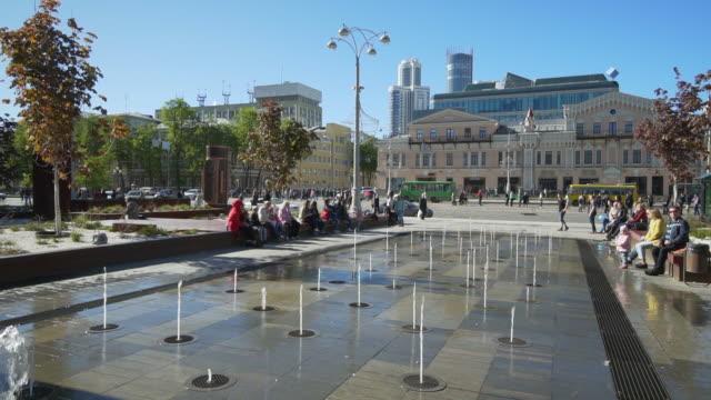 vidéos et rushes de slow motion: tourists sitting by fountain against buildings in city - yekaterinburg, russia - âges mélangés