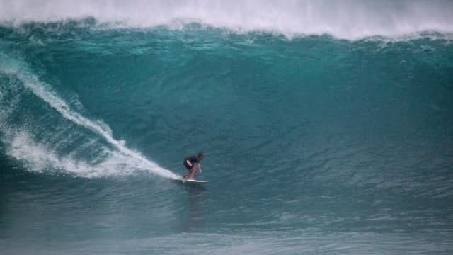 slow motion tracking a surfer on a giant crashing wave with enormous plumes of ocean spray - oahu, hawaii - overcast stock-videos und b-roll-filmmaterial