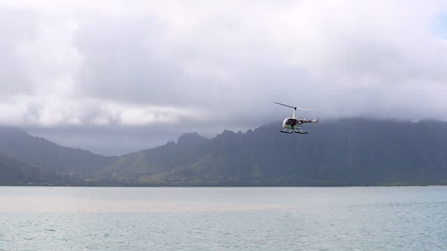 slow motion tracking of a helicopter as it flies over the sea under cloudy skies with steep mountains in the background - oahu, hawaii - hovering stock videos & royalty-free footage