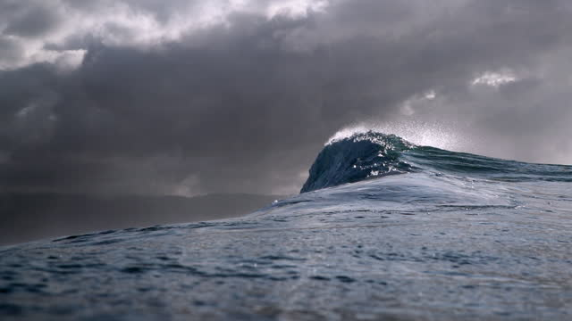 slow motion tracking of a large dark and breaking wave against a gray and stormy sky - oahu, hawaii - hawaii islands stock videos & royalty-free footage