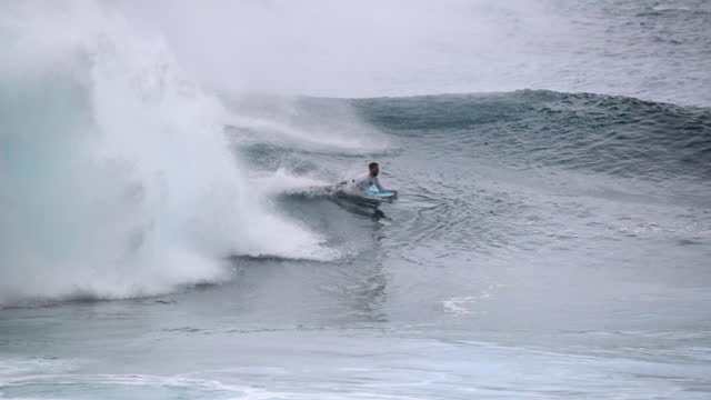 slow motion tracking of a surfer on his bodyboard riding a large crashing wave with other surfers paddling in the background - oahu, hawaii - other点の映像素材/bロール