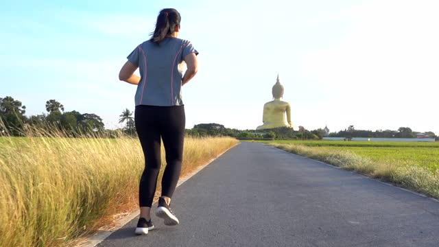 vídeos de stock, filmes e b-roll de rastreamento em câmera lenta aquém do exercício de mulher adulta média correndo na paisagem natural do campo de pastagem verde - calções de corrida