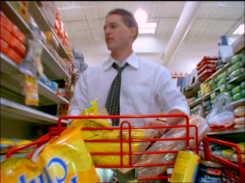 slow motion tracking shot businessman pushing shopping cart thru aisle of grocery store + checking watch