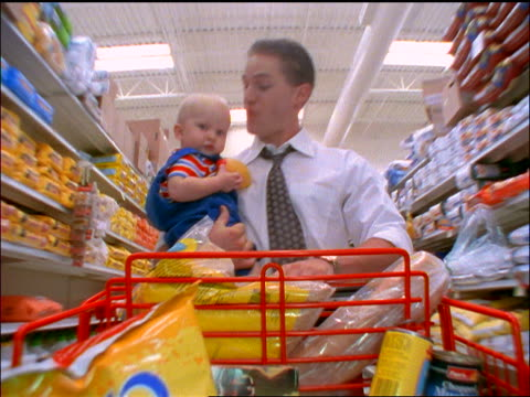 slow motion tracking shot businessman pushing shopping cart thru aisle of grocery store while holding baby boy