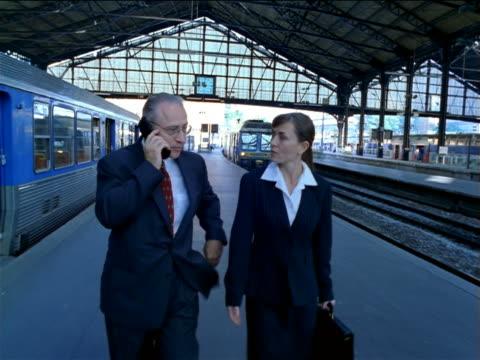 BLUE slow motion tracking shot Businessman + woman talk + walk in Gare de Lyon / man talks on cell phone / Paris
