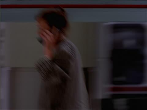 vídeos de stock e filmes b-roll de slow motion tracking shot businesswoman on cell phone walking through airport terminal - trabalhadora de colarinho branco