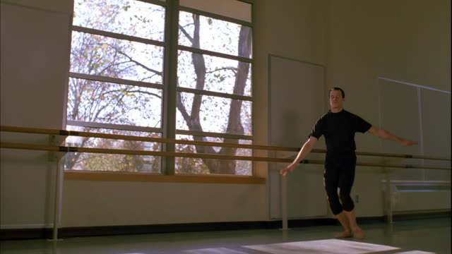 slow motion tracking shot male ballet dancer jumping by window - barre stock videos & royalty-free footage