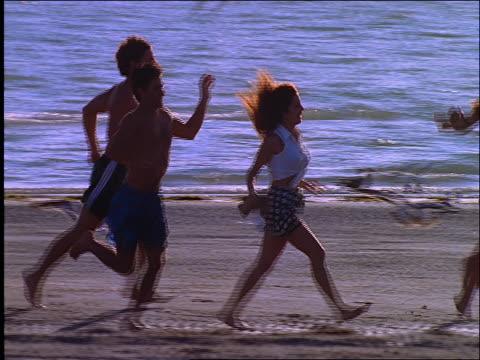 slow motion tracking shot of 2 men and 2 women running on beach - paar mittleren alters stock-videos und b-roll-filmmaterial