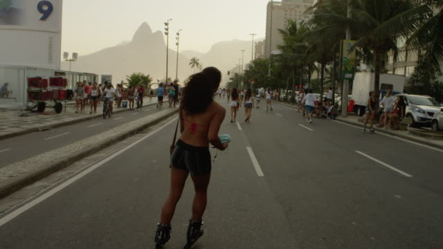 slow motion tracking shot of a brazilian girl rollerblading down avenida vieira souto - avenida stock videos & royalty-free footage