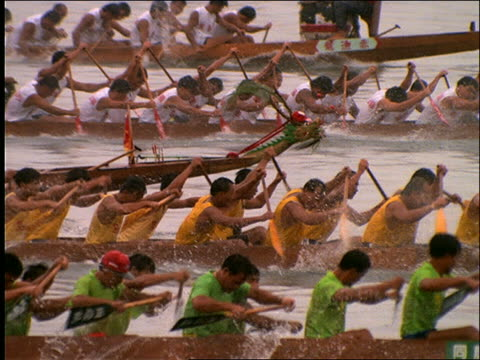 vídeos de stock e filmes b-roll de slow motion tracking shot of asian men rowing in dragon boat race / hong kong - cinematografia