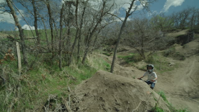 slow motion tracking shot of boy jumping hill on bicycle at bike park / salt lake city, utah, united states - bmxに乗る点の映像素材/bロール