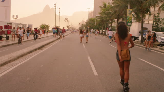 slow motion tracking shot of brazilian girl rollerblading down avenida vieira souto at dusk. - blade stock videos & royalty-free footage