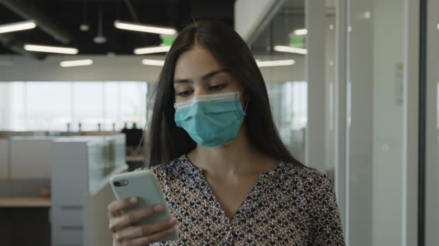 slow motion tracking shot of businesswoman wearing protective face mask texting / pleasant grove, utah, united states - brown hair stock videos & royalty-free footage