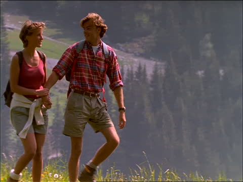 slow motion tracking shot of couple hiking on grassy hilltop (backpacks) - エコツーリズム点の映像素材/bロール