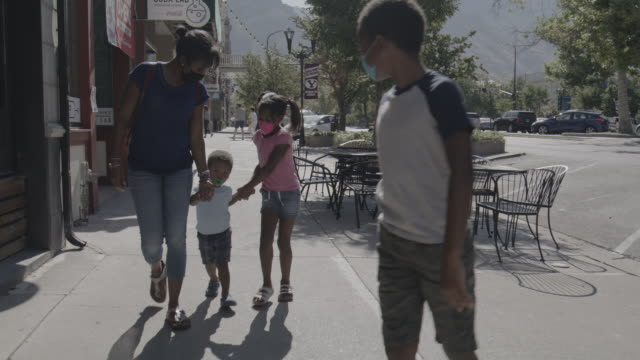 slow motion tracking shot of family wearing protective masks walking on city sidewalk / provo, utah, united states - baby boys stock videos & royalty-free footage