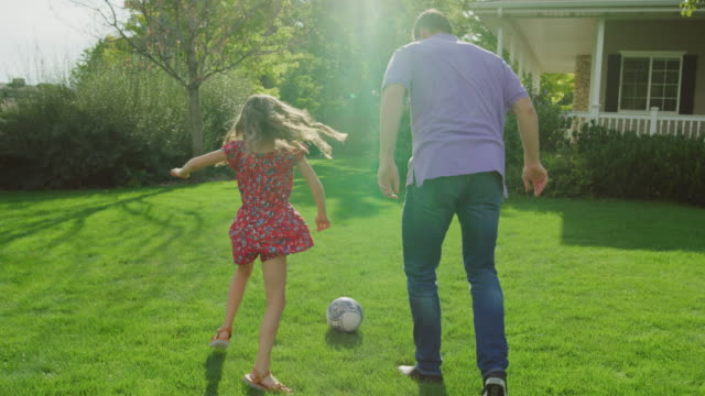stockvideo's en b-roll-footage met slow motion tracking shot of father and daughter playing soccer in yard / pleasant grove, utah, united states - schoppen lichaamsbeweging