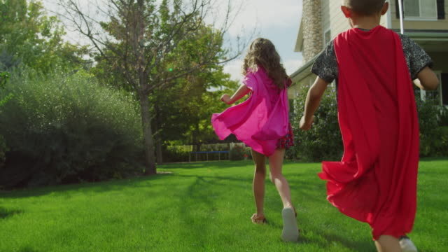 vidéos et rushes de slow motion tracking shot of girl and boy running on lawn in costumes / pleasant grove, utah, united states - grass