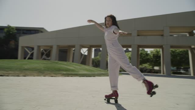 slow motion tracking shot of girl looking at camera while roller skating / salt lake city, utah, united states - utsträckta armar bildbanksvideor och videomaterial från bakom kulisserna