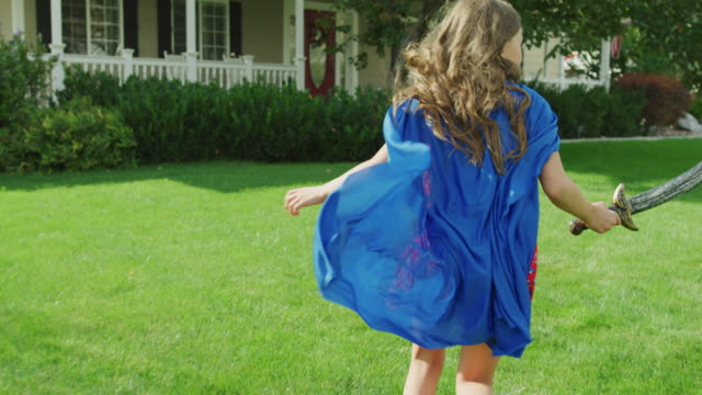 vídeos de stock, filmes e b-roll de slow motion tracking shot of girl running on lawn with cape and sword / pleasant grove, utah, united states - super herói