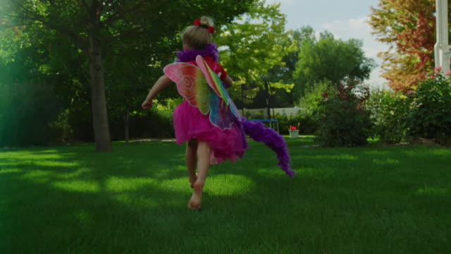 Slow motion tracking shot of girl running wearing fairy wings and waving sword / Pleasant Grove, Utah, United States