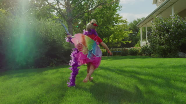 vidéos et rushes de slow motion tracking shot of girl running wearing fairy wings and waving sword / pleasant grove, utah, united states - zoom avant